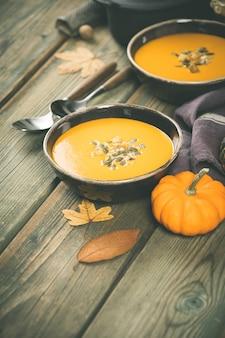 Zupa dyniowa na drewnianym stole, przytulne jedzenie koncepcja