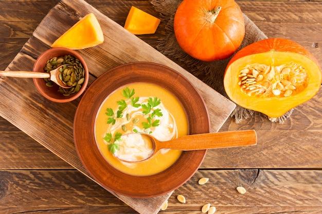 Zupa dyniowa na mleku kokosowym z pestkami dyni i pietruszką. żywność dietetyczna. drewniane tła. styl rustykalny.