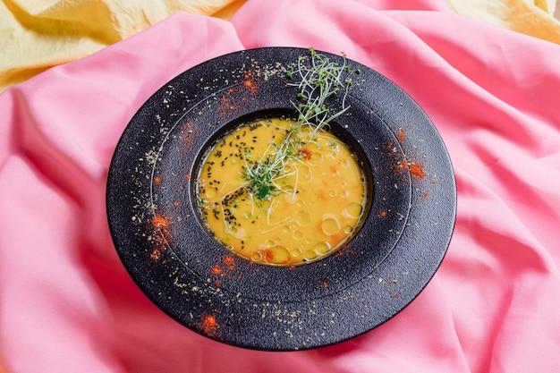 Zupa dyniowa na różowym tle, widok z góry,