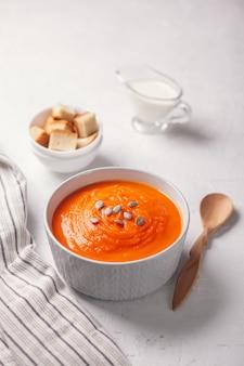 Zupa dyniowa-puree z bułką tartą, śmietaną i nasionami na białym tle.