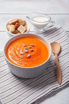 Zupa dyniowa-puree z bułką tartą, śmietaną i nasionami na ręcznik, białe drewniane tła.