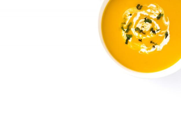Zupa dyniowa w białej misce na białym tle