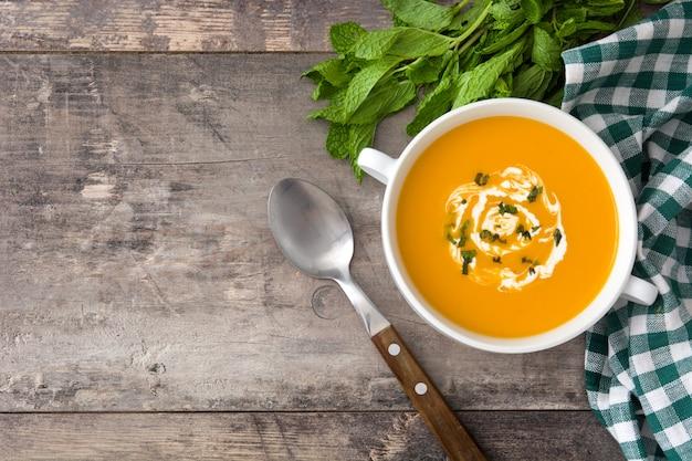 Zupa dyniowa w białej misce na drewnianym stole z miejsca na kopię