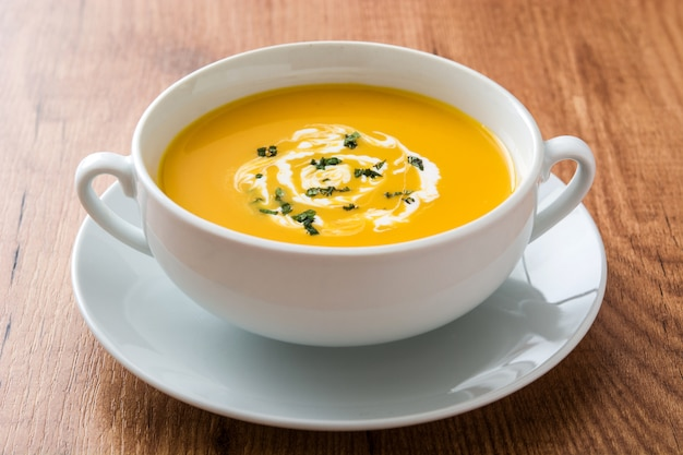 Zupa dyniowa w białej misce na drewnianym stole