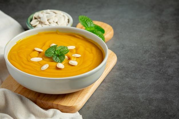 Zupa dyniowa w białej misce umieszczona na drewnianej desce do krojenia