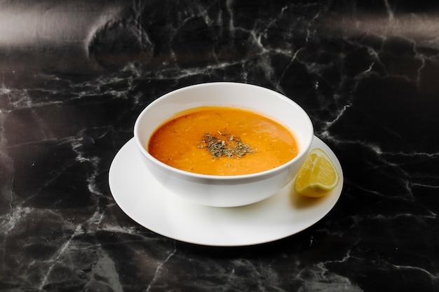 Zupa dyniowa w białej misce z ziołami i przyprawami, z plasterkiem cytryny dookoła.