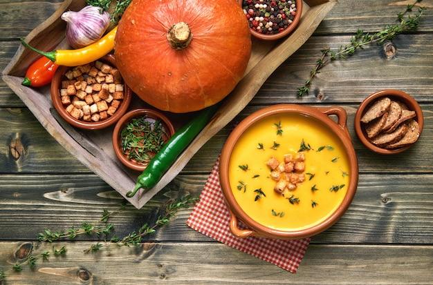 Zupa dyniowa w ceramicznej misce na rustykalnym drewnie podana z tymiankiem i grzankami, ze składnikami dookoła