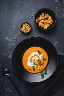 Zupa dyniowa w czarnej płycie ceramicznej na ciemnym tle drewnianych. tradycyjne jesienne jedzenie. przestrzeń kopii widoku z góry.