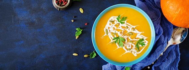 Zupa dyniowa w misce z dodatkiem pietruszki i pestek dyni. zupa wegańska jedzenie na święto dziękczynienia.