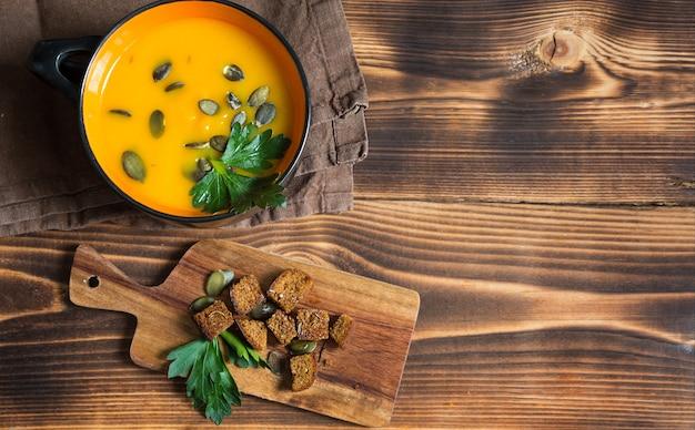 Zupa dyniowa w misce z nasionami i pietruszką na drewnianym tle
