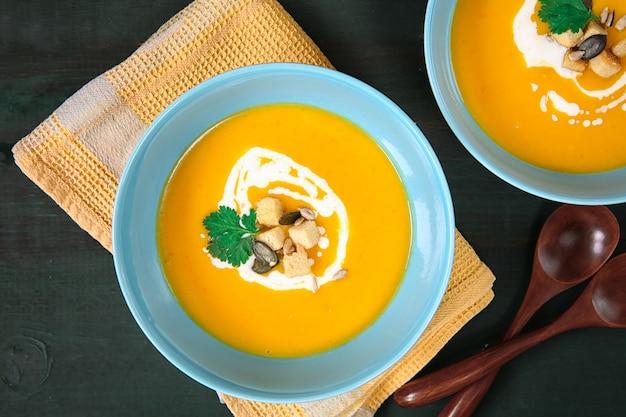 Zupa dyniowa z bliska na żółtej serwetce. dwa talerze gorącego jedzenia. dania sezonowe. jesień