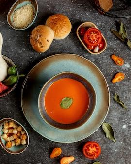 Zupa dyniowa z bułeczkami i pokrojonym pomidorem