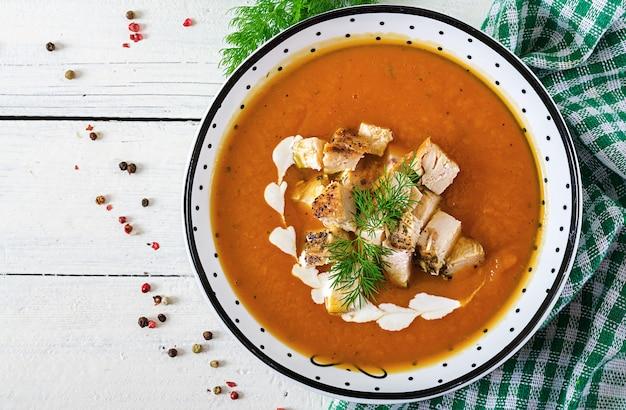 Zupa dyniowa z kawałkami mięsa z kurczaka. zdrowe jedzenie. obiad. widok z góry. leżał płasko