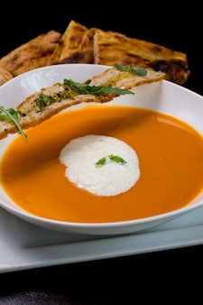 Zupa dyniowa z krakersami z pianki mlecznej krakersy rukoli widok z boku