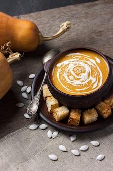 Zupa dyniowa z kremem i sezamem z grzankami na drewniane tła