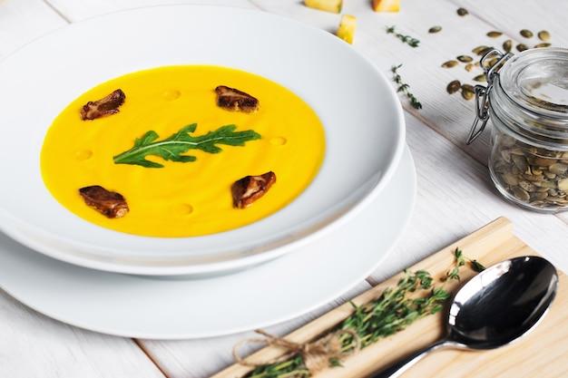Zupa dyniowa z nasionami i łyżką na stole.