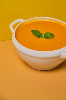 Zupa dyniowa zdobiona bazylią na pomarańczowym tle