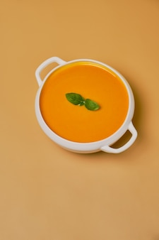 Zupa dyniowa zdobione bazylią na białym tle na pomarańczowym tle. monochromatyczny, minimalizm. widok z góry. skopiuj miejsce.