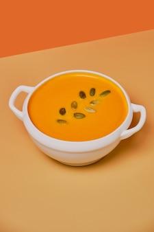 Zupa dyniowa zdobione pestkami dyni na białym tle na pomarańczowym tle. monochromatyczny, minimalizm. widok z góry. skopiuj miejsce.
