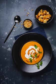 Zupa dyniowa ze śmietaną, kawałkami chleba i orzechami cedrowymi w czarnej płycie ceramicznej na ciemnym tle drewnianych. tradycyjne jesienne jedzenie. przestrzeń kopii widoku z góry.