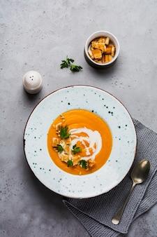 Zupa dyniowa ze śmietaną, kawałkami chleba i orzechami cedrowymi w szarym talerzu ceramicznym na szarym tle stołu. tradycyjne jesienne jedzenie. przestrzeń kopii widoku z góry.