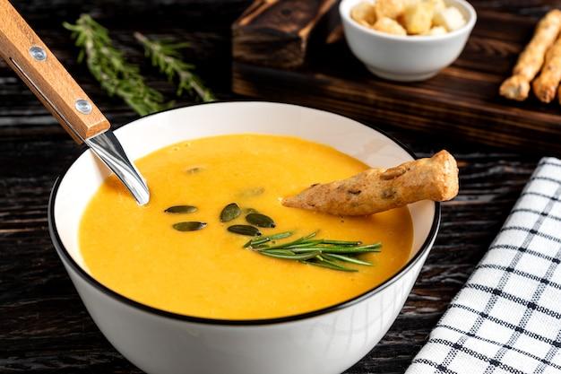 Zupa dyniowo-marchewkowa ze śmietaną, pestkami dyni, grzankami i paluszkami grossini na ciemnym tle drewnianych.