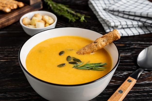 Zupa dyniowo-marchewkowa ze śmietaną, pestkami dyni, grzankami i paluszkami grossini na drewnianym tle dar k. styl rustykalny, selektywna ostrość.