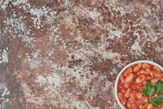 Zupa fasolowa w sosie pomidorowym w ceramicznym kubku.