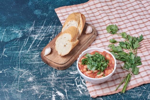 Zupa fasolowa w sosie pomidorowym z ziołami i pieczywem.
