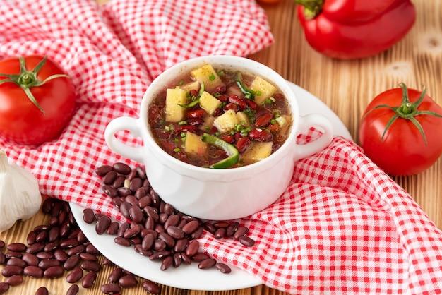 Zupa fasolowa z mięsem w białej ceramicznej misce.