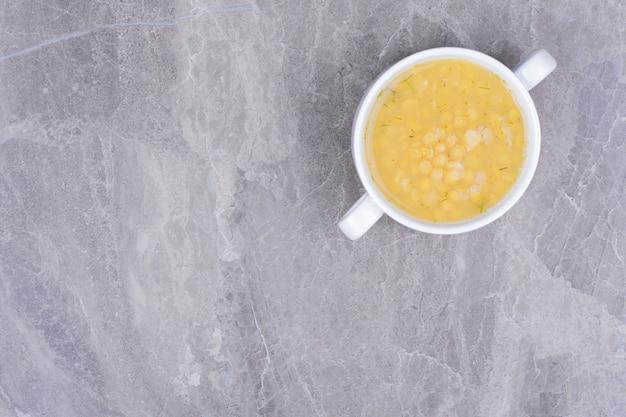 Zupa grochowa w białej ceramicznej misce na marmurze
