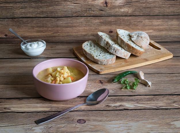 Zupa grochowa w misce na drewnianym stole. rustykalne jedzenie.