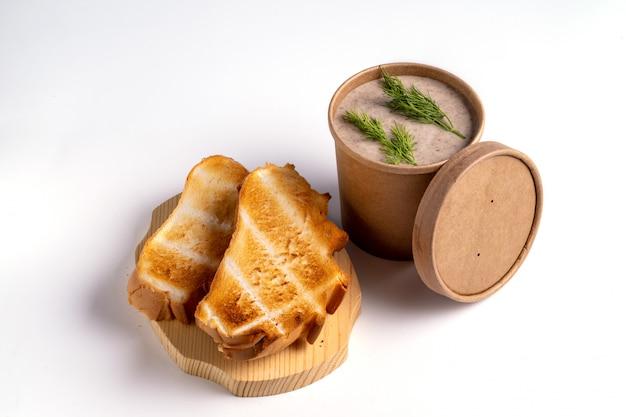 Zupa grochowa w papierowych jednorazowych kubkach na wynos lub dostawy żywności na niebieskim tle