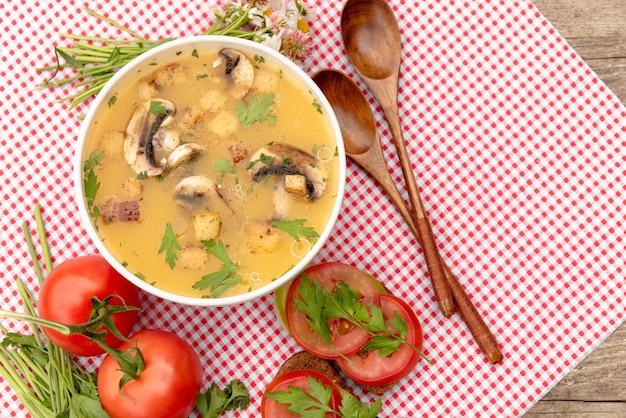 Zupa grzybowa na starym drewnianym stole z ziołami.