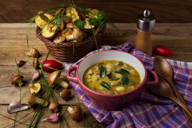 Zupa grzybowa w czerwonej misce i wiklinowym koszu na rustykalnym stole