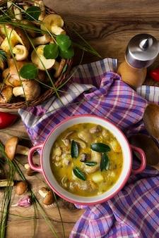 Zupa grzybowa w czerwonej rustykalnej miski i młynek do pieprzu, widok z góry.