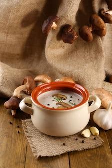 Zupa grzybowa w garnku, na drewnianym stole, na tle wory