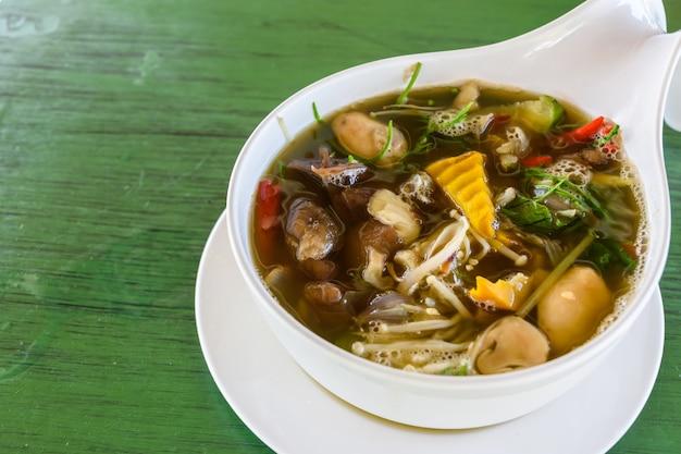 Zupa grzybowa w stylu tajskim na zielonym stole, tajskie lokalne jedzenie.
