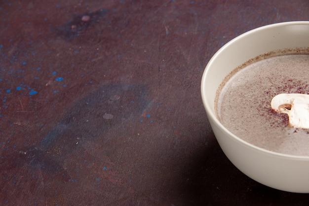 Zupa grzybowa z bliska z przodu wewnątrz płyty w ciemnej przestrzeni
