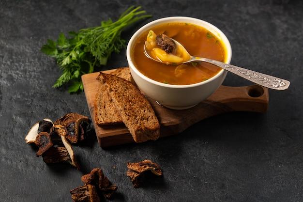 Zupa grzybowa z borowikami na desce na czarno.
