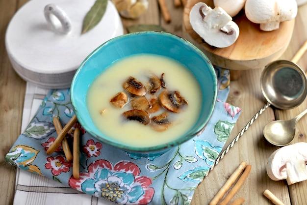 Zupa grzybowa z pieczarkami w niebieskim talerzu