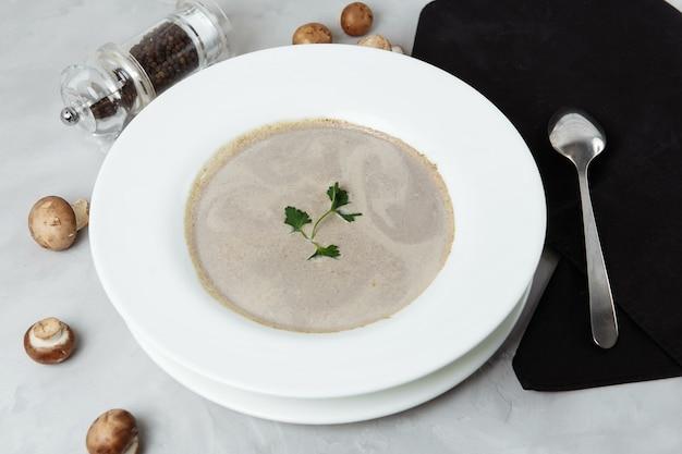 Zupa grzybowa z pietruszką na szarej przestrzeni, z bliska.