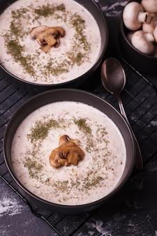 Zupa grzybowa. zupa ze świeżych grzybów. dwa talerze zupy krem z warzywami
