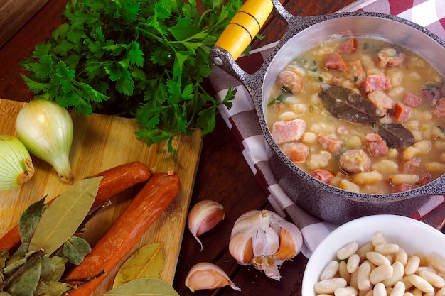 Zupa gulaszowa lub biała fasola z kiełbasą, warzywami, przyprawami i ziołami podawana na rustykalnej patelni na drewnianym stole
