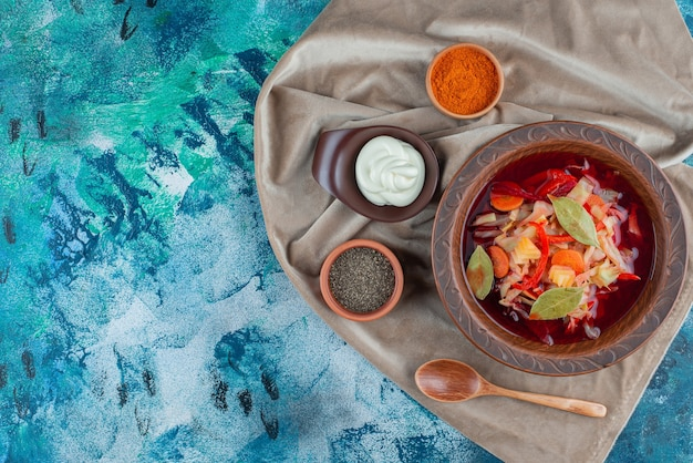 Zupa jarzynowa na talerzu na kawałkach tkaniny, na niebieskim tle.