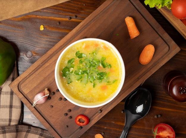Zupa jarzynowa rosół z kurczaka w misce jednorazowego użytku z zielonymi warzywami.