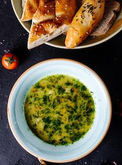 Zupa jarzynowa w bulionie z ziołami, pomidorem i chlebem.