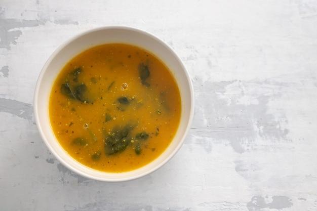 Zupa jarzynowa w misce na ceramicznym tle