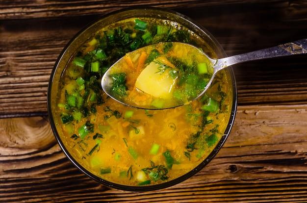 Zupa jarzynowa w szklanej misce na drewnianym stole. łyżka do zupy. widok z góry