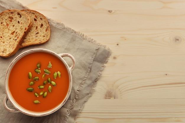 Zupa jarzynowa z dyni na drewnianym tle z organicznym chlebem marchewkowym na worze tekstylnym ręcznikiem. widok z góry z miejsca kopiowania.